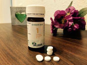Schuessler Salze 1 - Flasche und Tabletten auf braunem Holztisch